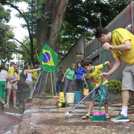 Pessoas se reuniram nesta manhã em mutirão para limpar a calçada do prédio onde Cármen Lúcia tem um apartamento Foto: Parceiro / Agência O Globo