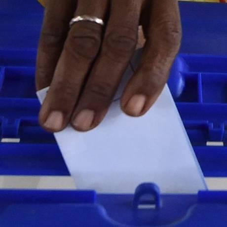 Mulher depoista voto em urna Foto: SIA KAMBOU / AFP