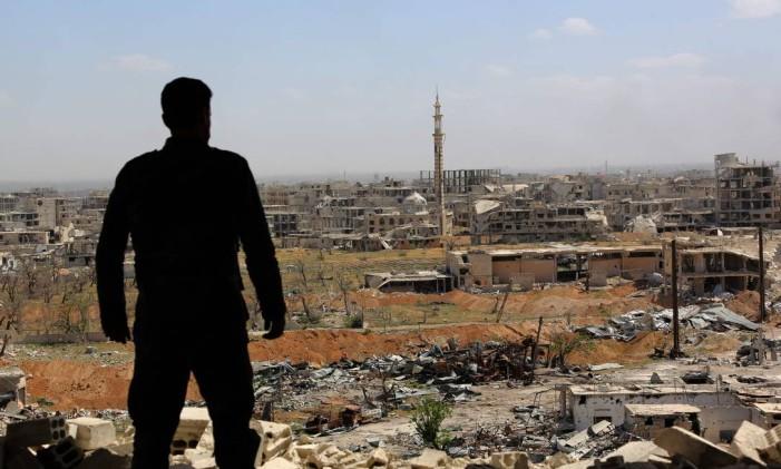 Soldado sírio olha para escombros de Ghouta Oriental: conflito no país opõe Ocidente e Rússia Foto: STR / AFP