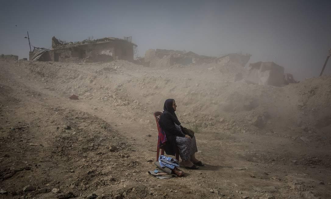 """Primeiro lugar na categoria Notícias Gerais, a foto """"A batalha por Mossul"""", de Ivor Prickett, do """"The New York Times"""", mostra Nadhira Aziz olhando sobre aquela que já foi a segunda maior cidade do Iraque após a sua retomada do Estado Islâmico; enquanto isso, trabalhadores da Defesa Civil retiravam os restos da sua irmã e da sua sobrinha, mortas num ataque em junho de 2017, que em setembro do mesmo ano ainda estavam dentro da sua casa na Cidade Velha Ivor Prickett / AP"""