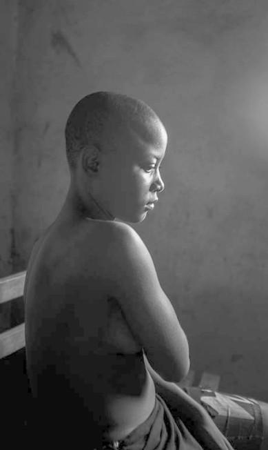 """Em imagem chamada """"Beleza Proibida"""",de Heba Khamis, que levou o primeiro lugar na categoria Questões Contemporâneas mostra adolescente de 12 anos escondendo os seus seios após a sua mãe ter passado um ferro sobre eles; esta é uma prática tradicional em Camarões para suprimir o desenvolvimento das meninas na puberdade, pois acredita-se que, assim, a maturidade será atrasada e os estupros serão evitados Heba Khamis / AP"""