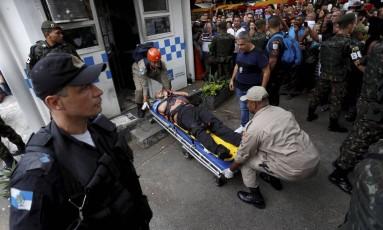 Jonny Neves dos Santos é levado por bombeiros para o hospital após ser agredido por esfaquear a ex-mulher Foto: Marcelo Theobald / Agência O Globo