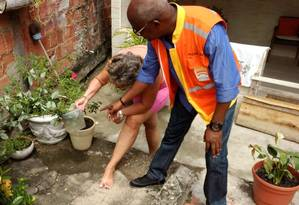 Prevenção. Agente da prefeitura orienta moradora do Barreto a eliminar água parada da vasilha de planta Foto: Divulgação/Prefeitura de Niterói