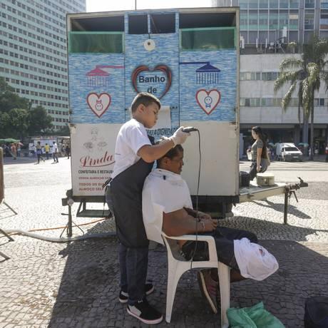 Henrique, de 10 anos, corta o cabelo de morador de rua: quem quiser pode ainda fazer a barba Foto: Gabriel de Paiva