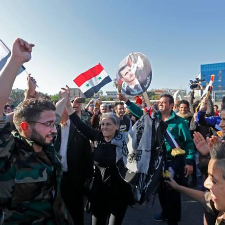 Sírios tremulam a bandeira nacional em uma praça de Damasco para condenar o ataque dos EUA, França e Reino Unido contra o regime sírio Foto: LOUAI BESHARA / AFP