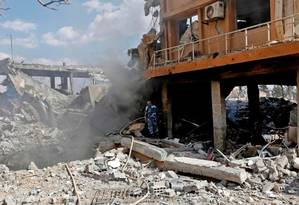 Soldado sírio inspeciona destroços de um prédio descrito como parte do Complexo do Centro de Estudos e Pesquisas Científicas (SSRC) no distrito de Barzeh, ao norte de Damasco, durante uma turnê de imprensa organizada pelo Ministério da Informação da Síria, neste sábado. Foto: AFP PHOTO / LOUAI BESHARA