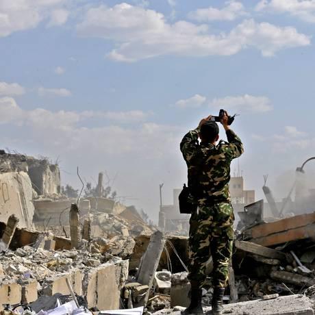 Soldado sírio inspeciona destroços do prédio do Centro de Estudos e Pesquisas Científicas no distrito de Barzah, ao norte de Damasco Foto: LOUAI BESHARA / AFP