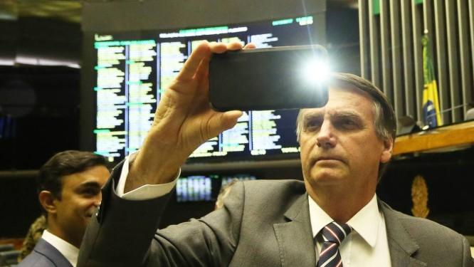 Bolsonaro filma sessão no plenário com celular Foto: Ailton de Freitas / Agência O Globo