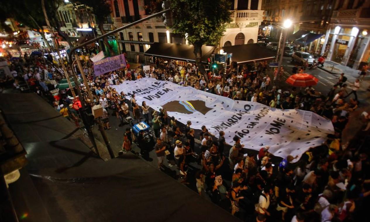 Desde sua morte, Marielle tornou-se símbolo de muitas manifestações políticas e culturais, sendo lembrada em diversos atos ao longo do ano. Na foto, manifestantes carregam faixa durante marcha em homenagem a Marielle Franco e Anderson Gomes em 14 de abril de 2018, um mês após o crime Foto: Brenno Carvalho / Agência O Globo