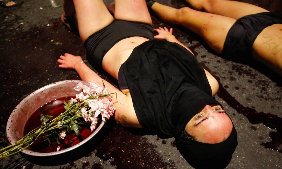 Manifestantes usaram tinta vermelha para manchar o asfalto durante passeata que marca um mês da morte de Marielle Franco e Anderson Gomes Foto: Brenno Carvalho / Agência O Globo