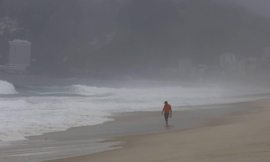 Homem caminha na areia da Praia de Ipanema Domingos Peixoto / Agência O Globo