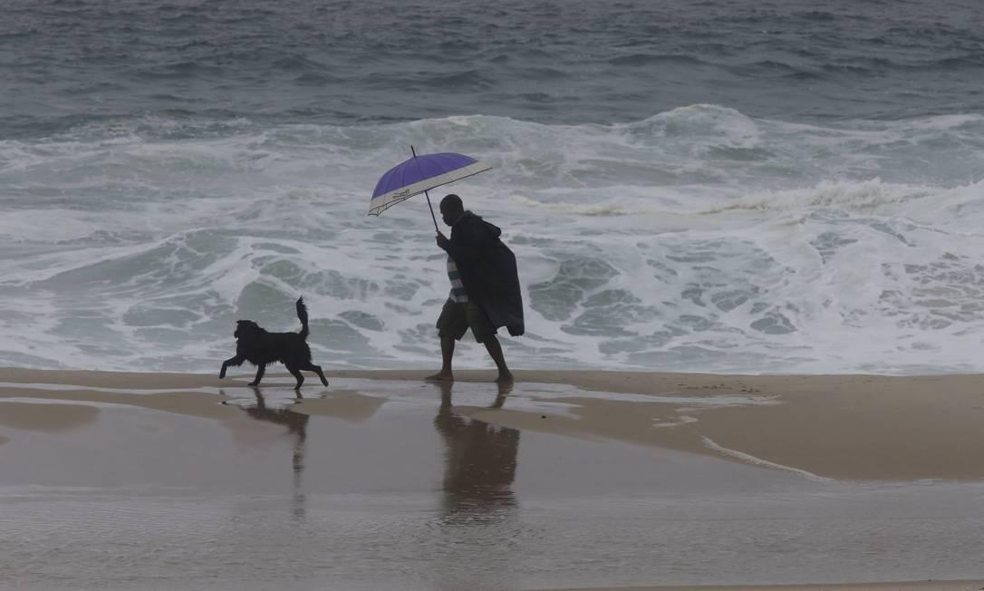Homem passeia com o cao na Praia de Ipanema Domingos Peixoto / Agência O Globo
