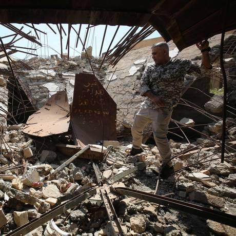 Combatente iraquiano checa tumba de ex-ditador Saddam Hussein, em ruínas, em Tikrit Foto: AHMAD AL-RUBAYE / AFP