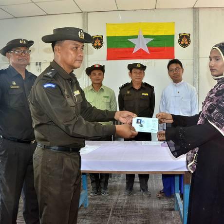 Na imagem divulgada pelo governo de Mianmar, autoridades aparecem entregando documentos de identificação para pessoas pertencentes à minoria étnica Rohingya, no que seria um processo de repatriação Foto: MYANMAR NEWS AGENCY / AFP