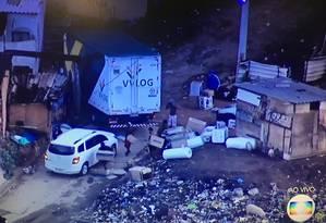 Bandidos levam a carga roubada até um carro branco Foto: TV Globo / Reprodução