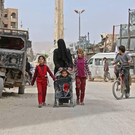 Civis caminham por Douma, cidade atingida por ataque Foto: STRINGER / AFP