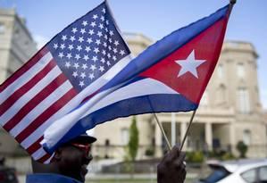 Homens carrega as bandeiras de Cuba e dos EUA Foto: Andrew Harrer / Bloomberg