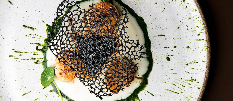 Nosso. Vieiras com com musseline de cará, coulis de espinafre, sauce diable, tuile negra (R$ 52). Foto: Tomas Rangel / Divulgação
