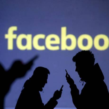 Pessoas usam seus celulares em frente à logomarca do Facebook Foto: Dado Ruvic / Dado Ruvic/Reuters/28-3-2018