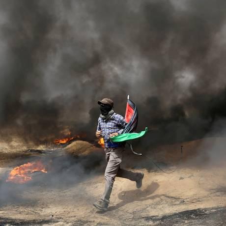 Manifestante palestino corre em área de tensão na fronteira com Israel, na quarta semana de protestos Foto: IBRAHEEM ABU MUSTAFA / REUTERS