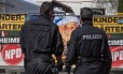 Policiais em epseram em frente à publicidade de festival neonazistana cidade de Ostritz, na Alemanha Foto: JOHN MACDOUGALL / AFP