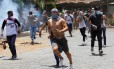 Manifestantes carregam pedras para tacar em policiais Foto: OSWALDO RIVAS / REUTERS