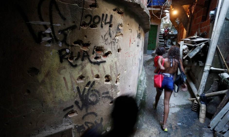 Jovem passa com filho no colo pela Linha da Morte, palco de intensos confrontos na Rocinha, a caminho da Macega Foto: Domingos Peixoto / Agência O Globo