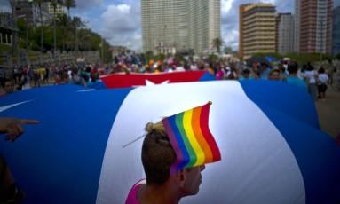 Luta pela tolerância. Cubano leva a bandeira do orgulho gay durante uma marcha LGBTI, em Havana: grupos reivindicam direitos e não são avessos a trabalhar com governo Foto: Ramon Espinosa / AP