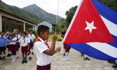 Déficit. Aluno hasteia a bandeira cubana em escola de Santo Domingo, Sierra Maestra: 16 mil professores teriam migrado para carreiras mais lucrativas Foto: ALEXANDRE MENEGHINI / Alexandre Meneghini/REUTERS/2-4-2018