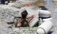 Menina toma banho em bueiro: 4 milhões de crianças moram em favelas no Brasil Foto: Marcelo Piu/02-12-2014