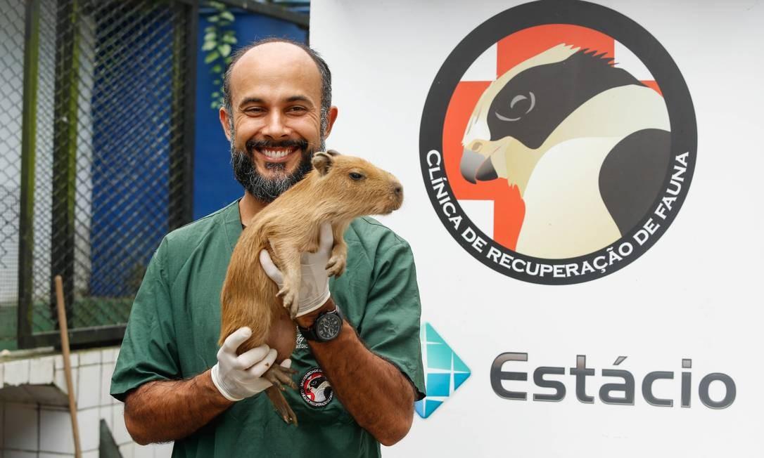 Jeferson com um filhote de capivara em frente à clínica que ajudou a criar logo que se formou Foto: Brenno Carvalho / Brenno Carvalho