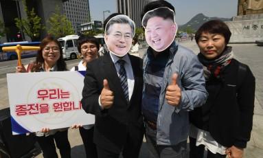 Ativistas sul-coreanos usando máscaras do presidente do país, Moon Jae-in (à esquerda), e do líder norte-coreano, Kim Jong-un, posam para fotos numa manifestação no centro de Seul para apoiar o diálogo na península Foto: AFP / JUNG YEON-JE