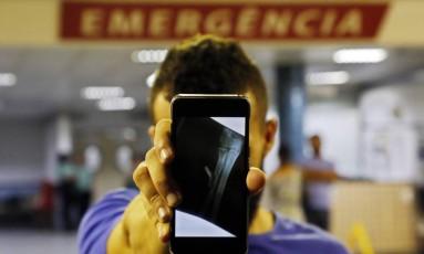 Parente segura imagem de radiografia da menina que mostra o projétil alojado Foto: MARCOS DE PAULA / Agência O Globo