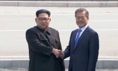 Líderes das Coreias se cumprimentam na abertura da cúpula: momento histórico Foto: AFP
