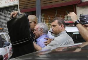 O segurança presidencial protege o presidente Michel Temer durante protestos de populares, no Largo Paissandu, onde desabou um prédio Foto: Nelson Antoine / AP