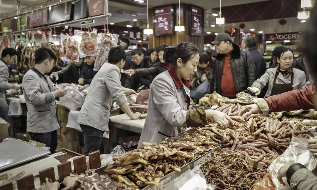 Atendentes de um supermercado vendem carne em Xangai: com o consumo maior, produtores têm dado aos rebanhos cada vez mais antibióticos, o que faz com que a população crie resistência a bactérias Foto: Bloomberg/Qilai Shen/22-1-17