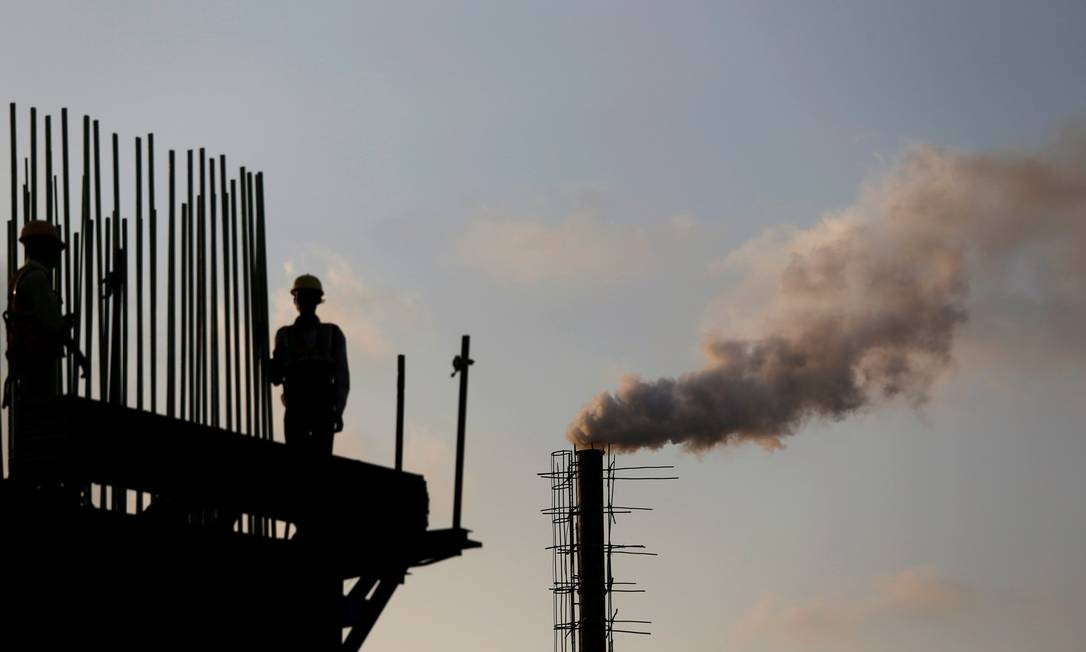Trabalhodores de uma obra perto de uma chaminé industrial que contamina o ar, em Bombaim, na Índia Foto: FRANCIS MASCARENHAS / REUTERS
