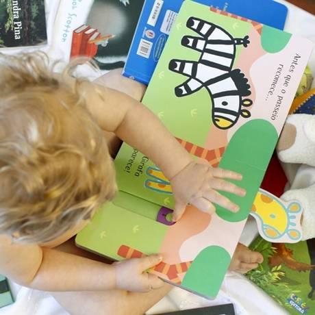 Livros com páginas grossas são ideais para bebês com cerca de 6 meses de idade, para que eles possam virar as páginas Foto: Agência O Globo