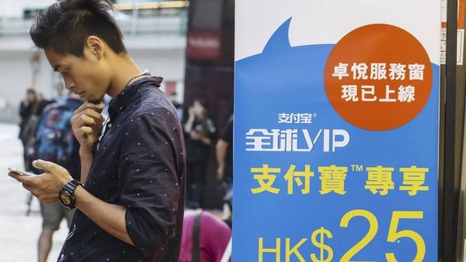 Jovem usa smartphone ao lado de anúncio do Ant Financial Services Group Foto: Anthony Kwan / Anthony Kwan/Bloomberg