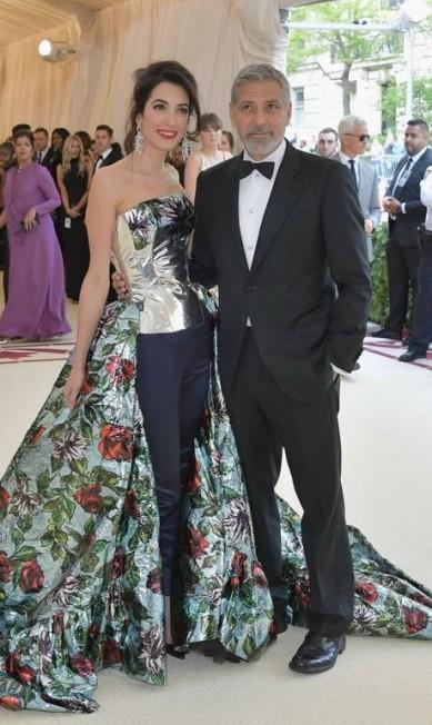 """O evento mais esperado do ano no mundo da moda reuniu gente do calibre deste casal da foto. Amal Clooney e George Clooney foram algumas das estrelas que prestigiram o Baile do Met 2018, que celebra a exposição """"Heavenly Bodies: Fashion & The Catholic Imagination"""", do Costume Institute do Metropolitan Museum, em Nova York Neilson Barnard / AFP"""