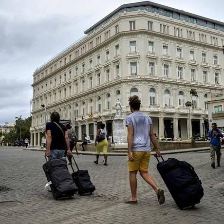 Turistas em frente ao Manzana Kempinski Hotel, em Havana, Cuba Foto: YAMIL LAGE / AFP