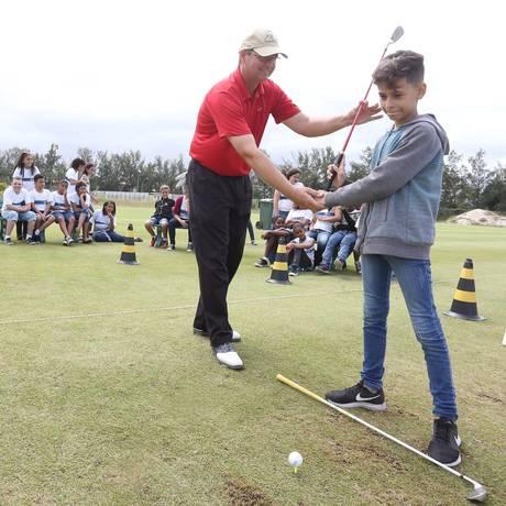 Projeto leva estudantes de escolas públicas para conhecer o Campo Olímpico de Golfe, na Barra da Tijuca. À direita, o estudante Thiago Mendonça, da Escola Honduras, arrisca a primeira tacada. Foto: Freelancer / Agência O Globo