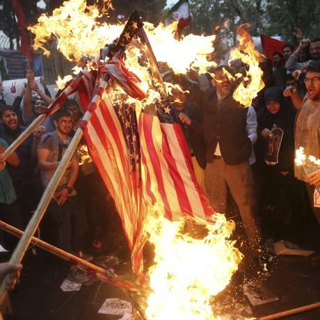 Revolta. Manifestantes queimam bandeira americana diante da embaixada dos Estados Unidos em Teerã, após saída de Washington do acordo sobre o programa nuclear iraniano Foto: Vahid Salemi/AP