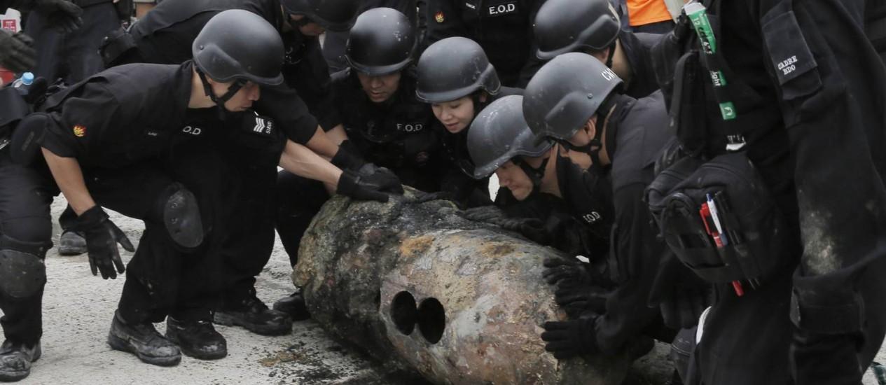 Esquadrão antibomba carrega explosivo após desativá-lo em Hong Kong Foto: Kin Cheung / AP