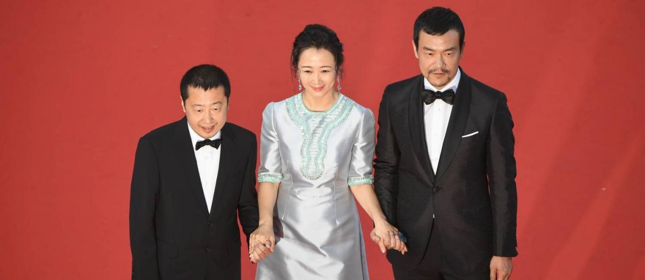 """O ator chinês Liao Fan e a atriz Zhao Tao chegam à Croisette com o diretor Jia Zhang-ke para a exibição de """"Ash is Purest White"""" Foto: ANTONIN THUILLIER / AFP"""