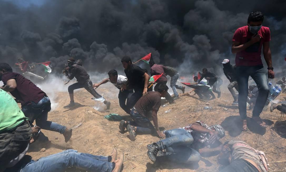 Manifestantes palestinos procuram se proteger das bombas de gás lançadas pelas forças israelenses: eles tentavam se aproximar da fronteira Ibraheem Abu Mustafa / REUTERS