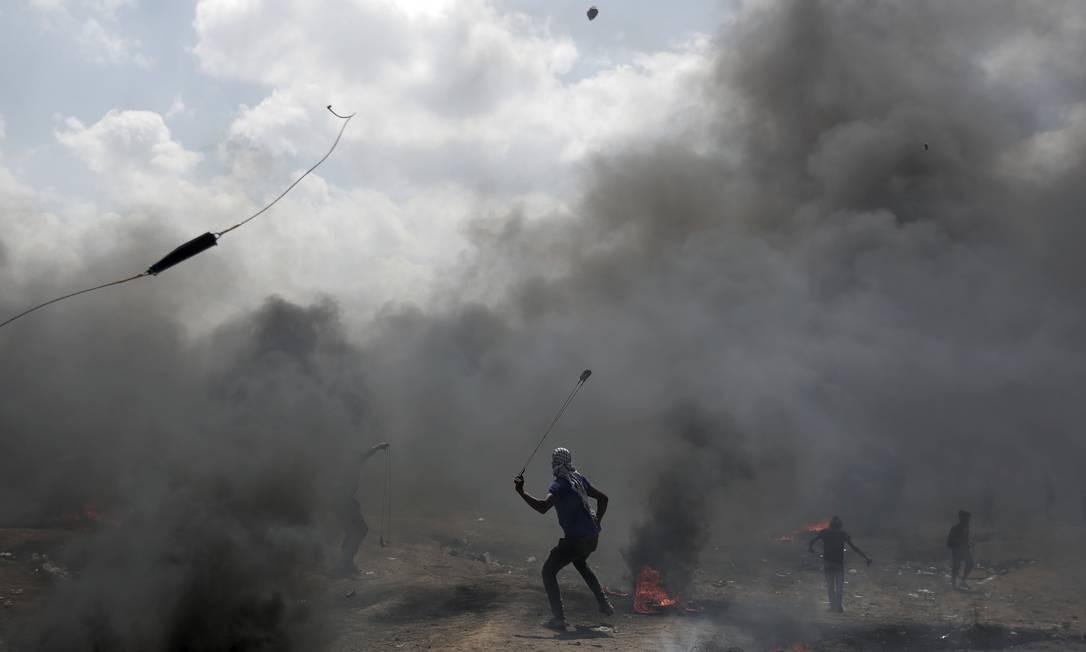 Manifestante lança pedra na direção de tropas israelenses durante protesto em Gaza. Hospitais estão superlotados Khalil Hamra / AP