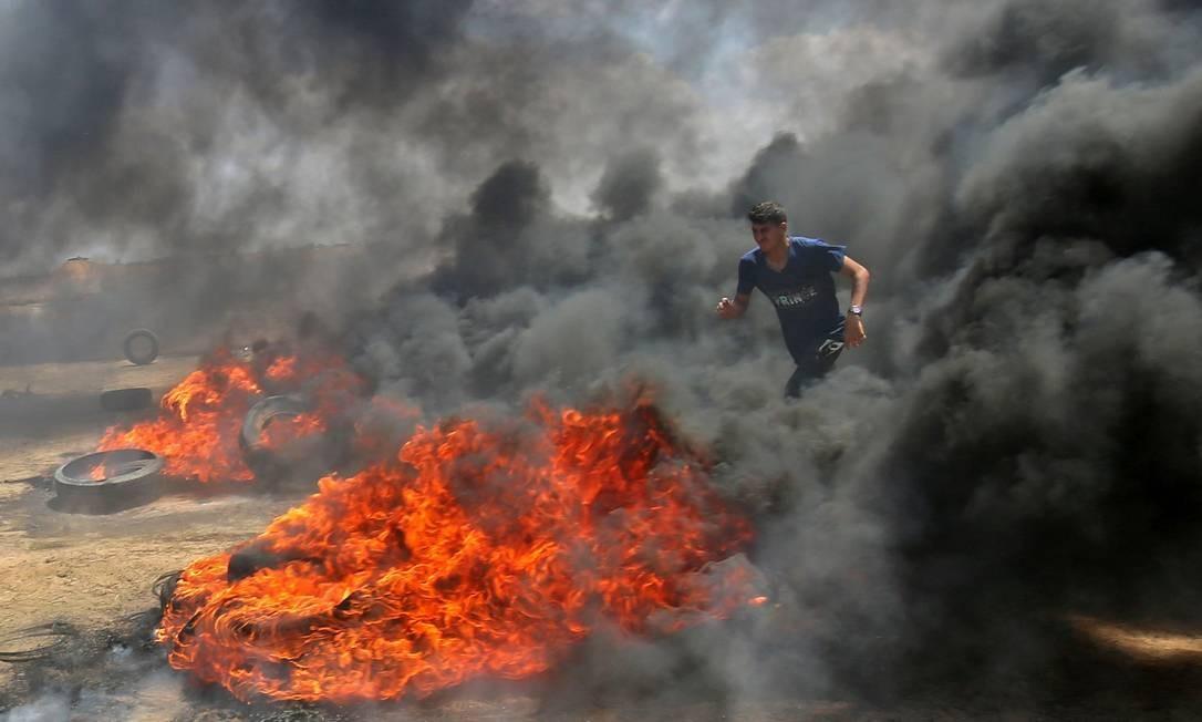 Homem caminha entre a fumaça dos pneus queimados durante o protesto contra Israel: transferência da embaixada americana de Tel Aviv para Jerusalém acirrou ainda mais os ânimos Said Khatib / AFP