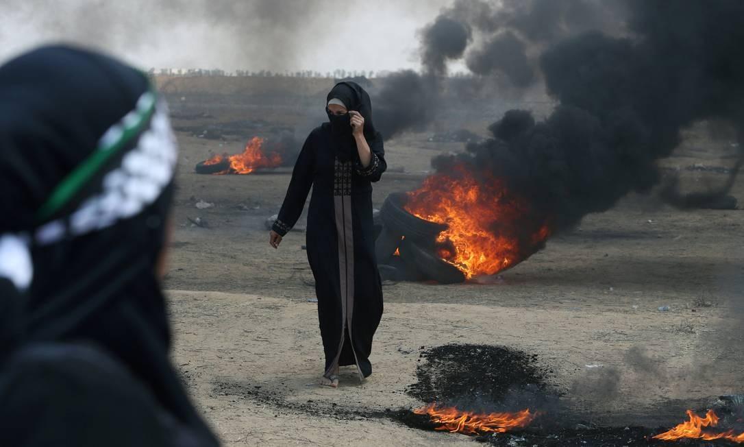 Uma manifestante caminha no meio do fogo após a resposta violenta de Israel ao protesto dos paletinos na Faixa de Gaza. Os palestinos gostariam de ter Jerusalém Oriental como capital de seu futuro Estado Ibraheem Abu Mustafa / REUTERS