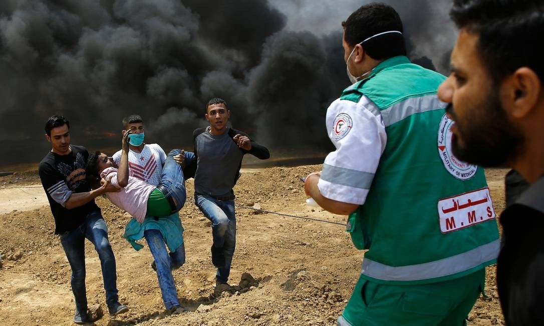 Palestinos carregam ferido durante confronto com as tropas de Israel Mohammed Abed / AFP